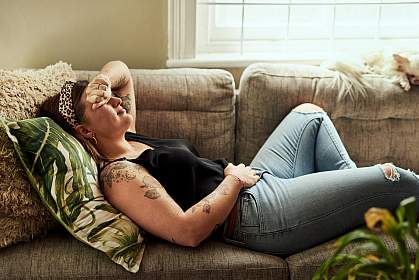Woman lying on sofa holding her stomach