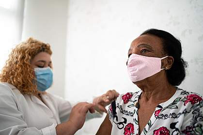 Older Black woman getting a vaccination