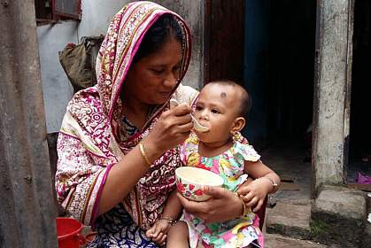 Mother feeding young child