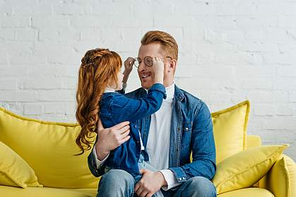 Red-haired daughter and father playing his with glasses while sitting on sofa