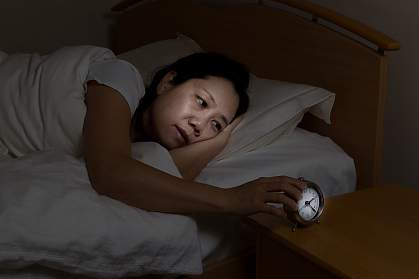 Woman in bed with eyes open touching clock on nightstand