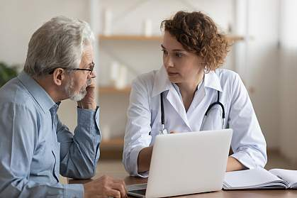 Female doctor speaking to older male patient