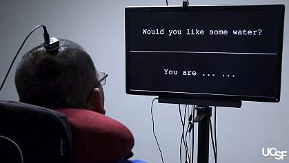 Rear view of man with an electrode array in his head watching a screen with words.