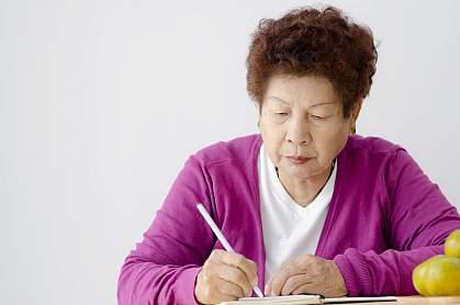 Asian senior woman writing in book