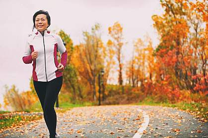 Mature Asian woman running in a park among colorful fall foliage