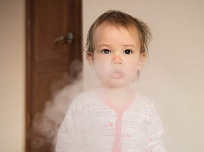 Young girl in a cloud of cigarette smoke