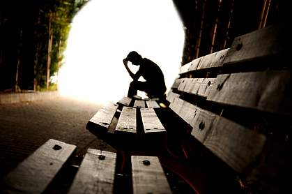 Person with head in hands on a deserted bench