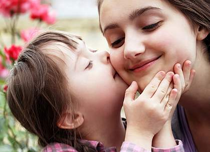 Child with Down Syndrome kissing the cheek of an adult.