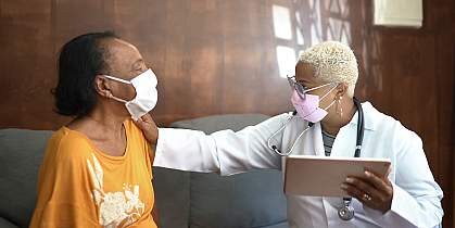 Doctor talking to senior female patient while being in a home visit