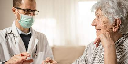 Happy senior woman listening as her doctor is explaining therapy details during house call visit