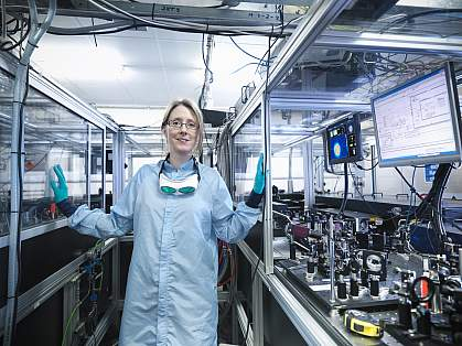 Portrait of female scientist by monitors with laser beam profiles and LabView code - stock photo