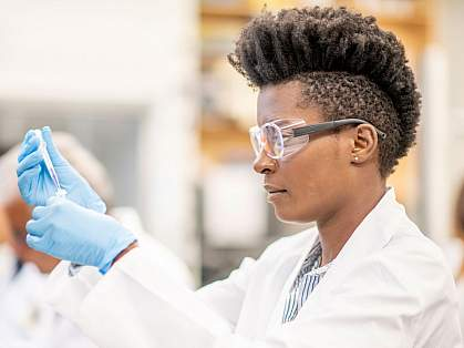 A woman in a lab coat and goggles experimenting in a lab.