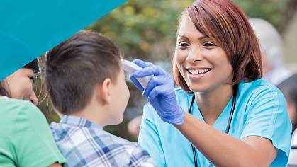 Smiling healthcare worker taking the temperature of a young boy.