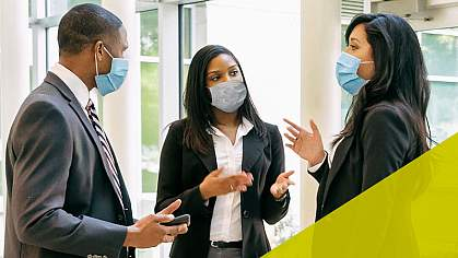Four professionally dressed individuals wearing medical face masks talking and referencing tablets they are holding.