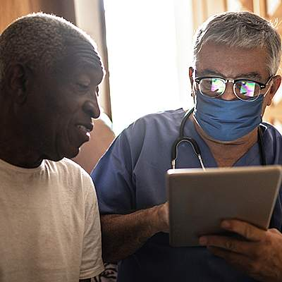 Doctor entering data into a tablet while talking with a patient