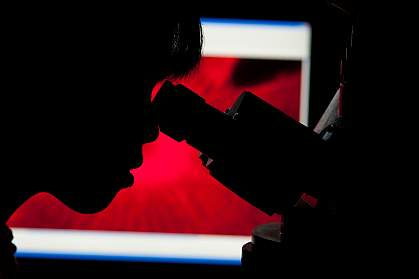 A researcher looking through a microscope.
