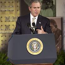 President George W. Bush standing at a podium.