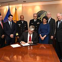 Acting Health and Human Services (HHS) Secretary Eric D. Hargan signs the declaration of a nationwide public health emergency on the opioid crisis, as requested by the President.  Standing from left to right: Assistant Secretary for Preparedness and Respo