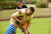 A man playing football with children.