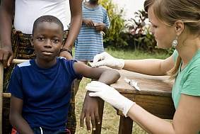 An American health worker preparing to give a African boy an injection.