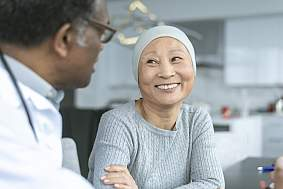Beautiful Korean woman with cancer smiles at doctor