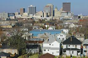 Cityscape with suburban homes in the foreground and a city skyline in the background.