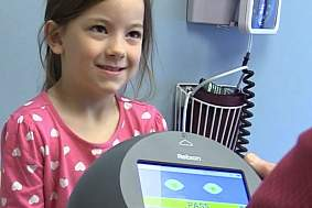 Female child smiles facing person holding screening device in a medical setting
