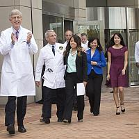 hoto of Francis Collins, Anthony Fauci and Nina Pham leaving the Clinical Center
