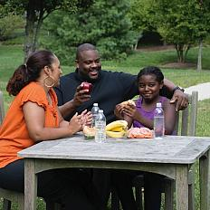 Family eating healthy snacks at a table outside.