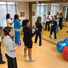 Women in a class working out with dumbbells in front of a mirror.