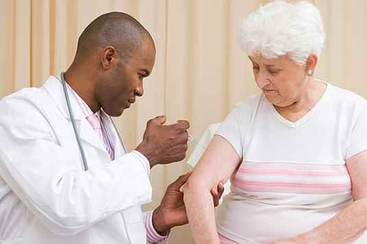 Doctor administering the avian H5N1 influenza vaccine to a woman.
