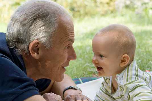 A senior man and baby looking into each other's eyes.