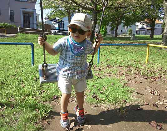 A younb boy on a swing.