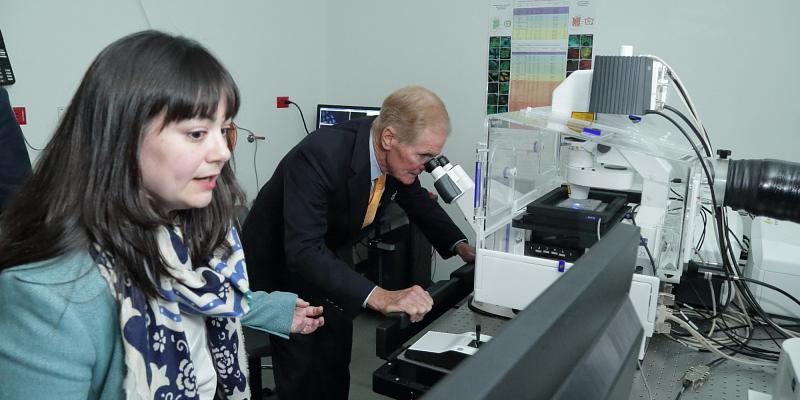 Dr. Shireen Sarraf, Postdoctoral Research Associate fellow, National Institute of Neurological Disorders and Stroke, and Senator Bill Nelson (FL), viewing advanced imaging technology in the confocal microscopy room.