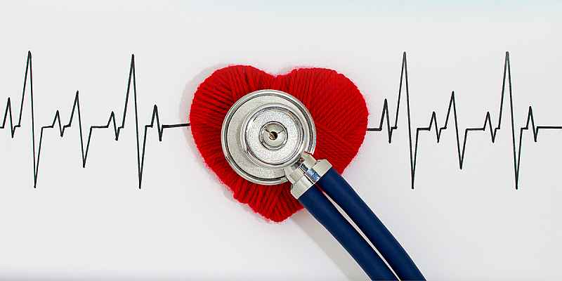 Stethoscope overlaid on a red heart and electrocardiogram