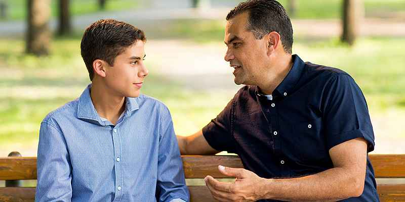 photo of a father and son sitting on a bench