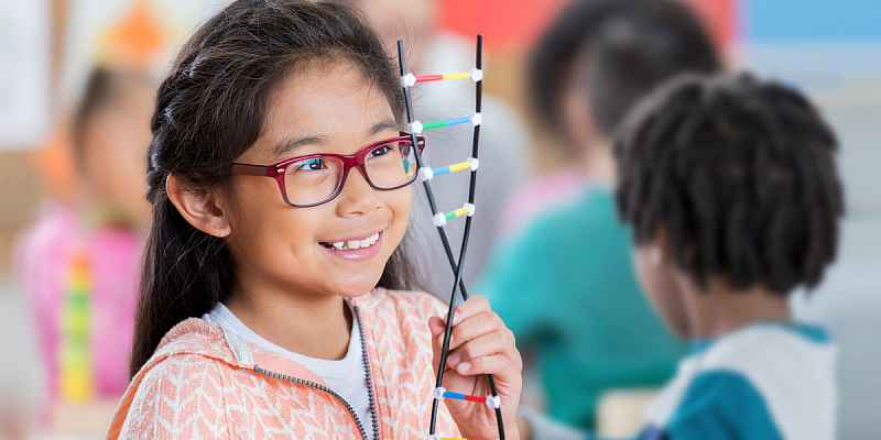 A photo of children, a little girl holding a DNA model is in the forefront of the image.