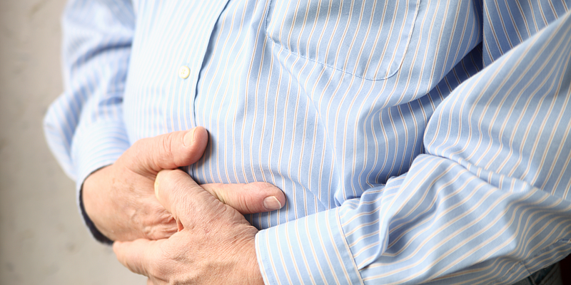Man in dress shirt holding his stomach with both hands