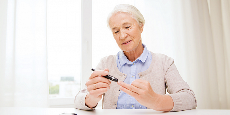 Woman with diabetes checking her blood glucose level with a blood glucose meter.