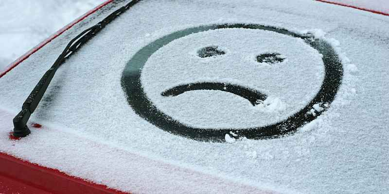 Sad face drawn on snow-covered car window.