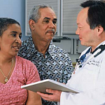 Photo of a doctor speaking with a couple.