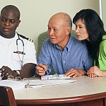 Photo of a doctor speaking with a patient and a family member.