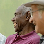 Video screenshot of three mature men talking together.
