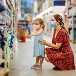 Portrait of a mature woman with her daughter wearing a protective mask shopping in a supermarket