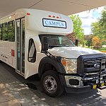 An NIH campus shuttle bus arrives at a stop.