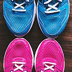 A pair of blue sneakers above a pair of pink sneakers.
