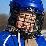 A young boy wearing sports equipment.