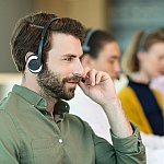 Information specialists at a contact center wearing phone headsets