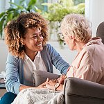 A caregiver assisting a senior woman in her home