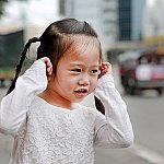 A child plugging her ears due to loud street traffic